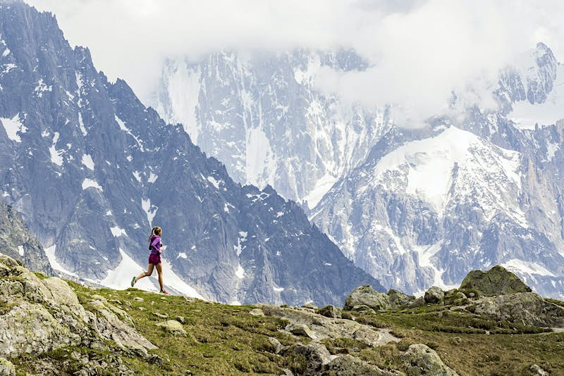 Girl trail running in Chamonix around the Chesery lake (Lac des Cheserys). In the background many mountains are visible.