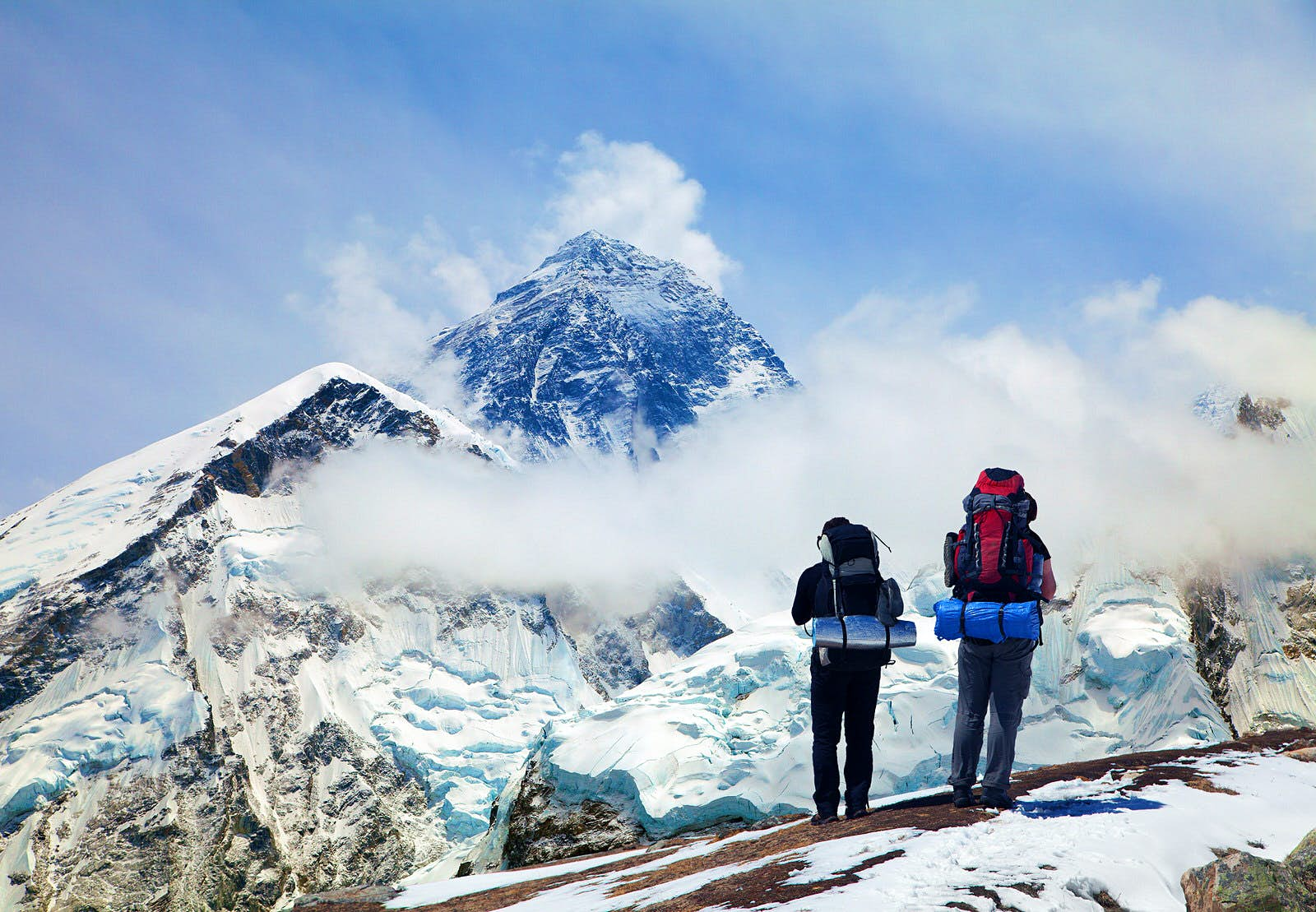 Panoramic view of Mount Everest from Kala Patthar with two tourists on the way to Everest base camp.