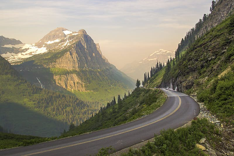A road curves around a misty mountain as another snow-covered peak appears between two crags