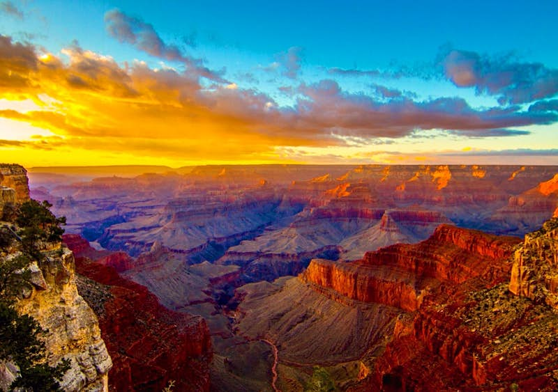 An orange sunset to the left highlights the deep canyon walls and red and purple shadows at the Grand Canyon