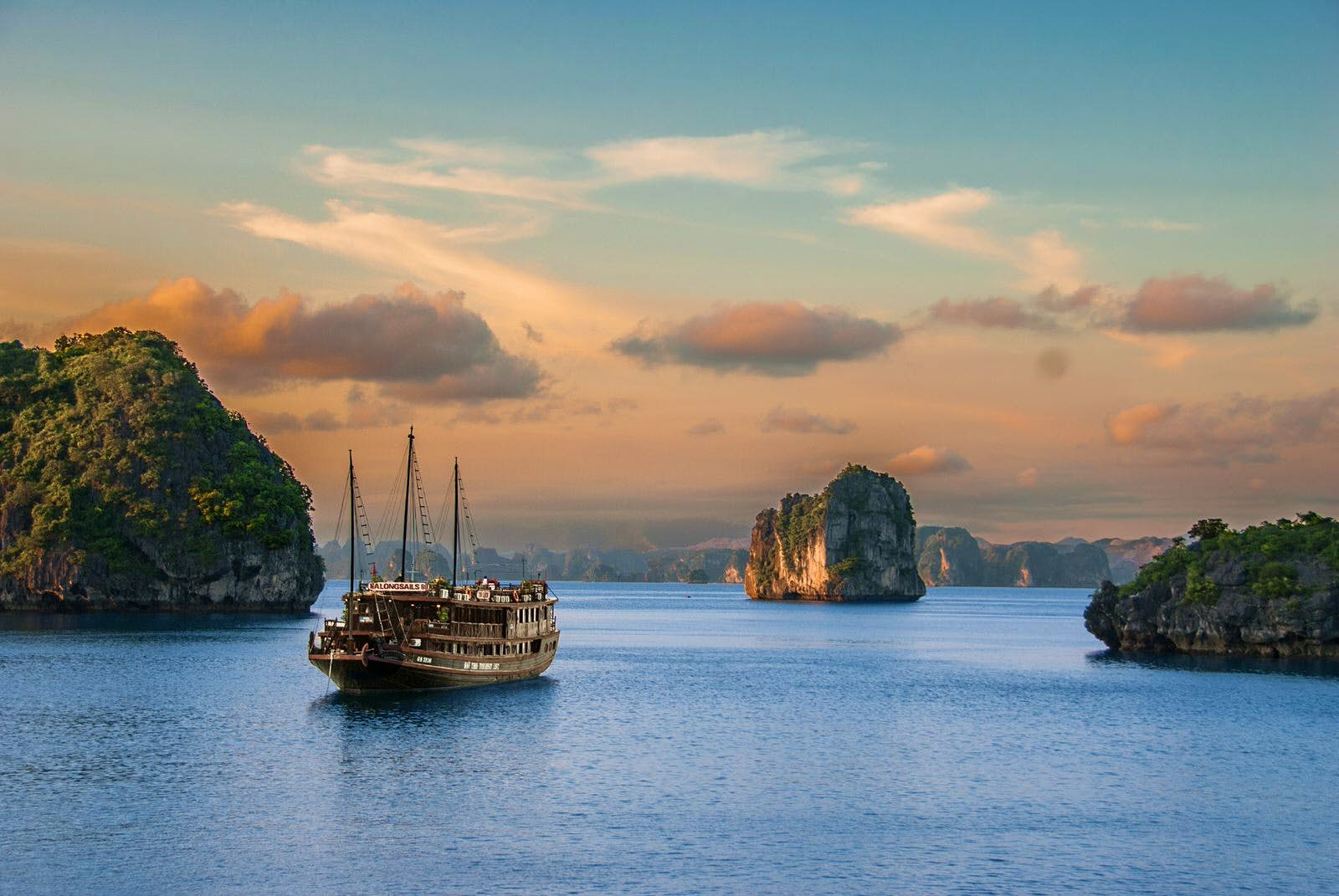A traditional boat sails on the waters of Halong Bay, with limestone pillars protruding from the water surrounding it