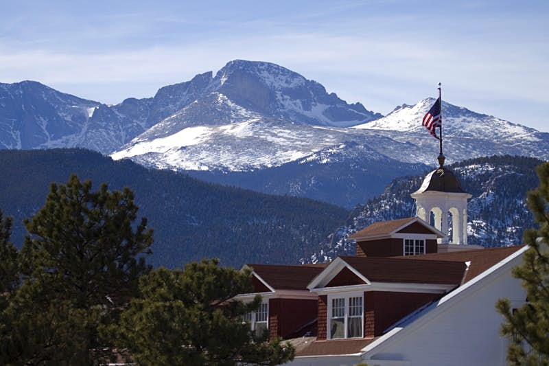 Rising to 14,255 feet Longs Peak towers over the historic 1907 Stanley Hotel in Estes Park, Colorado. The peak stands in Rocky Mountain National Park