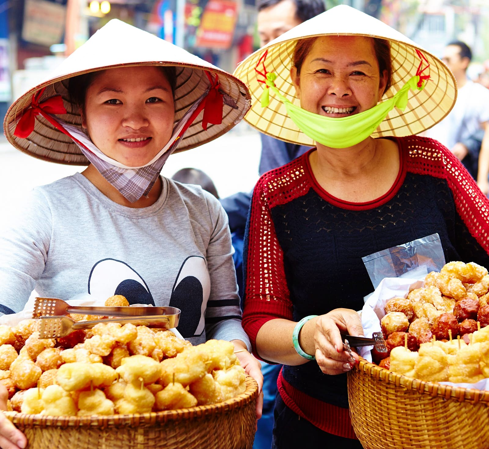 Two women pose with baskets of street food in Hanoi. Both women are wearing conical hats, which are common in the country.