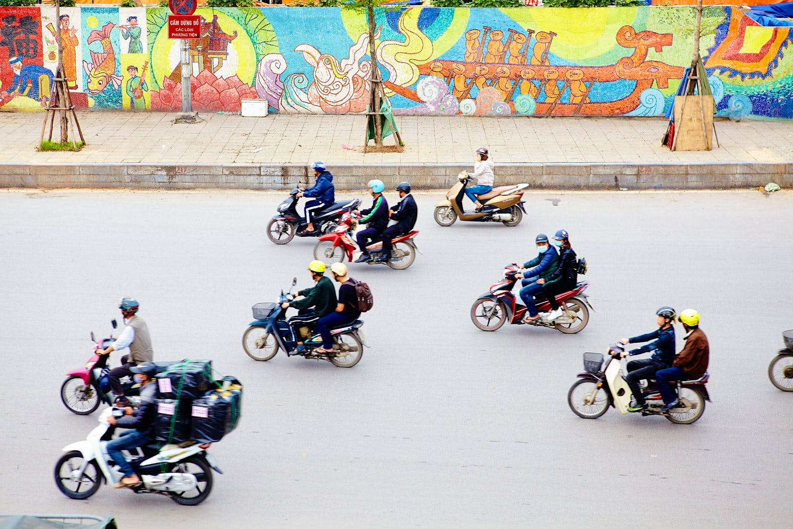 Aerial view of a selection of mopeds driving down a concrete street in Hanoi