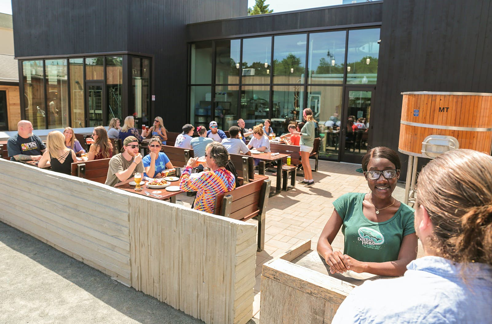 Hostess checks in a guest at Dogfish Brewing in Delaware, with a modern, concrete patio full of people in the background. Many craft breweries in the US now feature outdoor patio spaces.