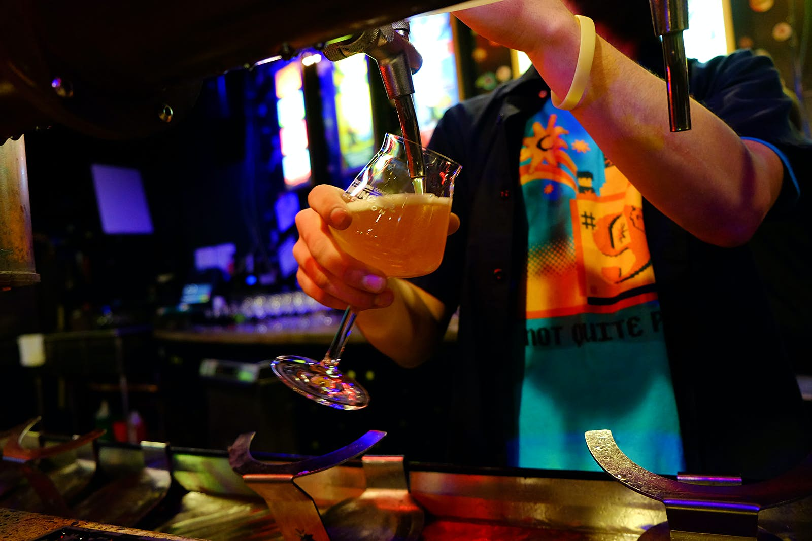 Close-up of man pouring beer into a tulip-shaped glass at a wooden bar at Magic Hat brewing. Many craft breweries in the states also have amazing food menus.