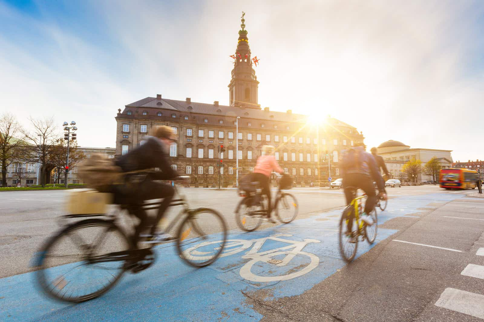 Blurred cyclists ride on a bike lane in Copenhagen, with the sun setting over Christiansborg palace.
