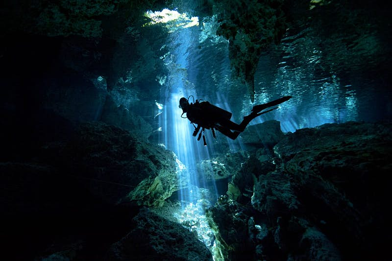 A scuba diver is silhouetted in front of a shaft of light as they explore a cenote (sinkhole) in Mexico
