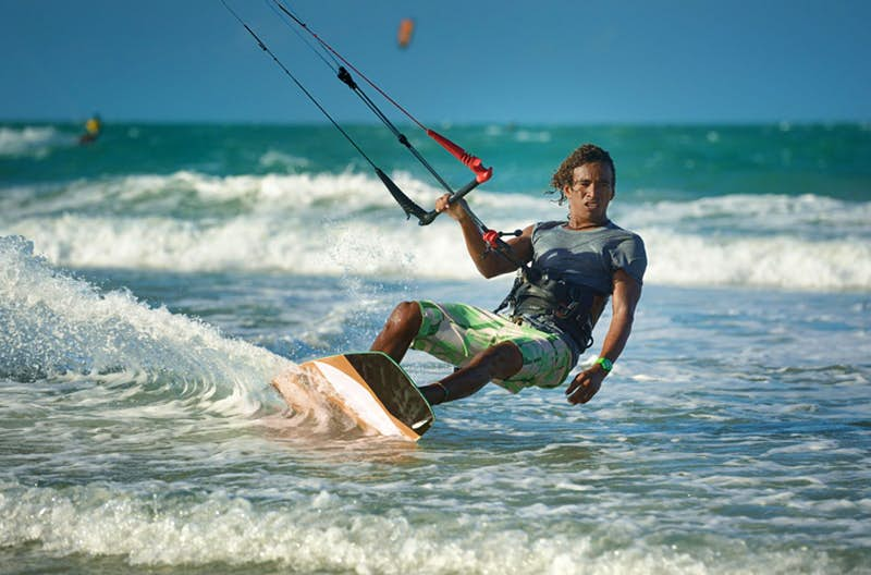 A male kitesurfer with long hair leans away from his board with one hand holding on to the handle of his kite equipment