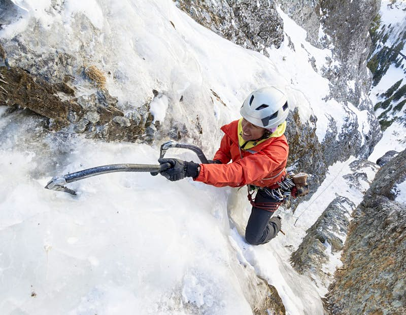 A woman wearing a red jacket and a helmet smiles as she hauls herself up an icy precipice assisted by her ice axe