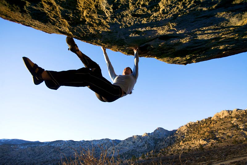 A woman, without equipment to support her, hangs below a rocky overhang