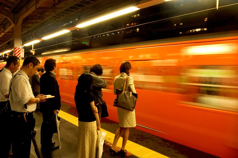 Passengers wait to board a train at Shinjuku Station