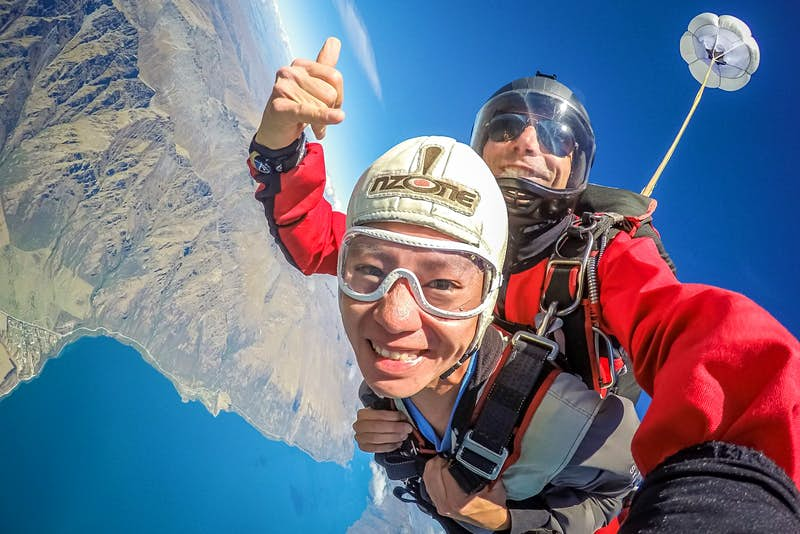The skydiver smiles at the camera during freefall, while the instructor gives a thumbs up. The land and lake can be seen below