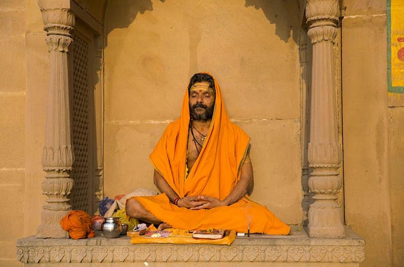 A sadhu (holy man) mediates in the warm sunshine