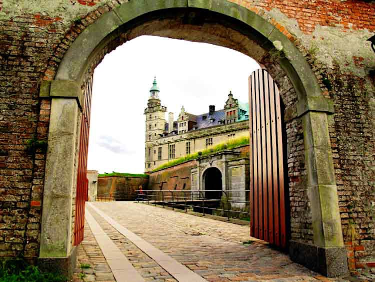Turrets and gables of Elsinore (Helsingor) Castle, made famous in Shakespeare's 'Hamlet,' framed in the castle gate. Image by Tom Horton, Further To Fly Photography / Flickr / Getty Images.