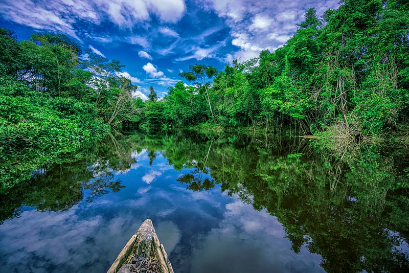 A wooden canoe drifts down a glassy Nanay river with Amazon forest on both shores. The photo is taken from the body of the canoe, with just the tip in frame. The cloudy blue sky is reflected in the still water.