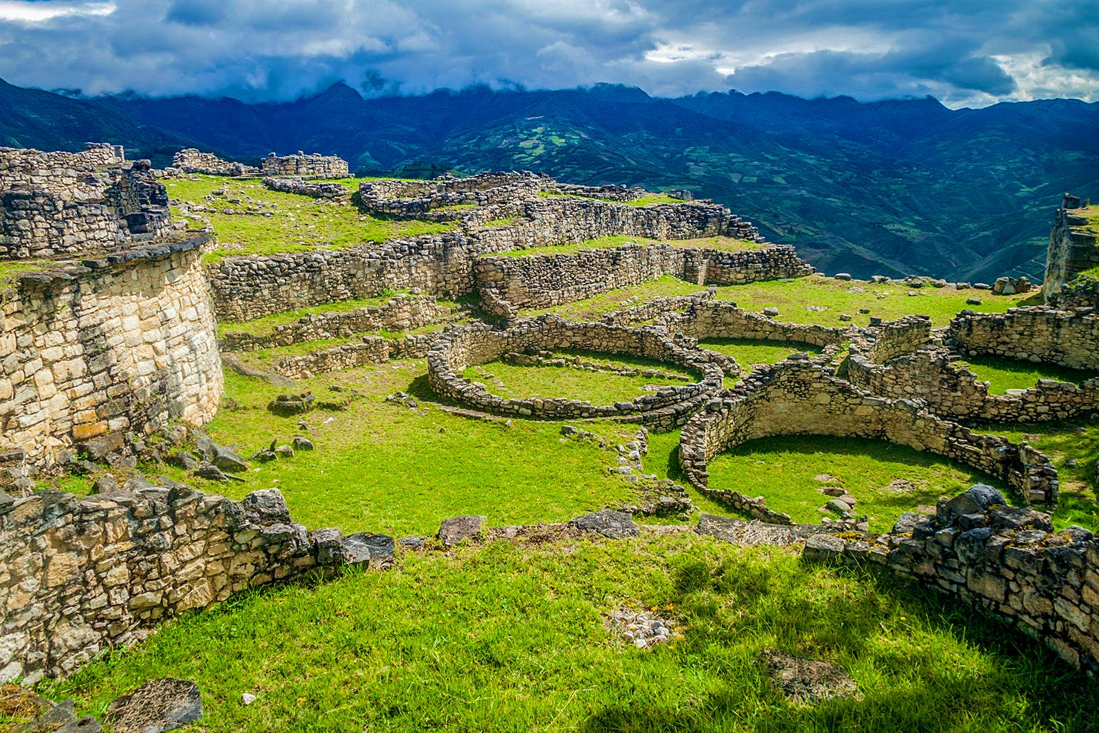 Peru travel - A view of the Kuelap citadel site, with a grassy field punctuated by foundations of stone walls and round homes