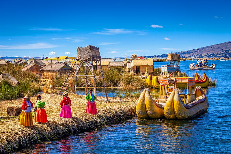 Four women in brightly colored, traditional skirts stand on a shoreline close to two curved boats made out of reeds