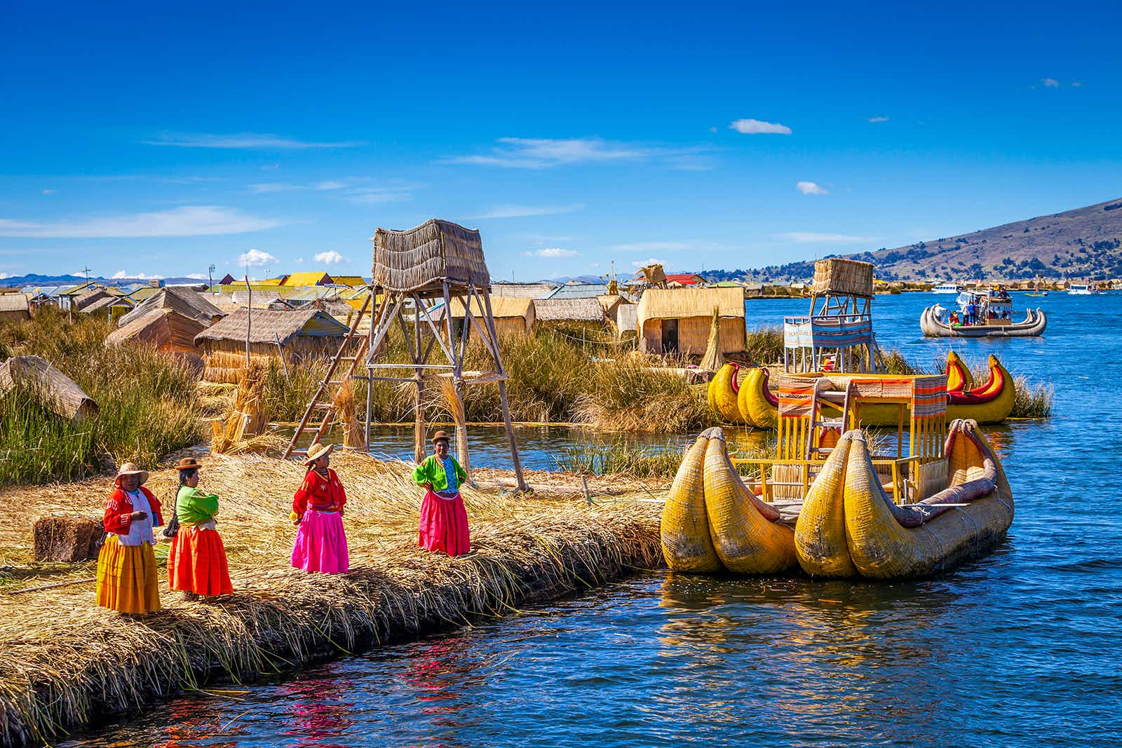 Women stand on Uros, one of Lake Titcaca's floating island © saiko3p / Getty Images