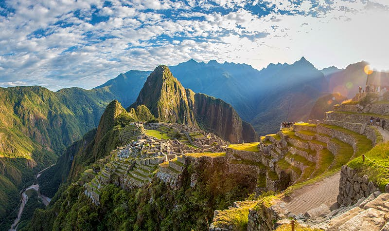 A panoramic shot as the sun rises over Machu Picchu. The blue sky is dotted with clouds and the terraced slopes along the trail are awash with greenery.