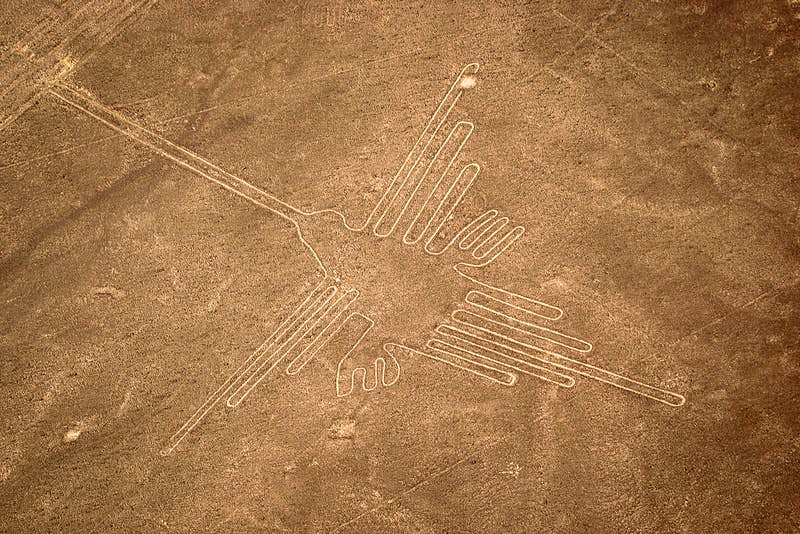 An aerial shot of a hummingbird carved into red dirt near Nazca