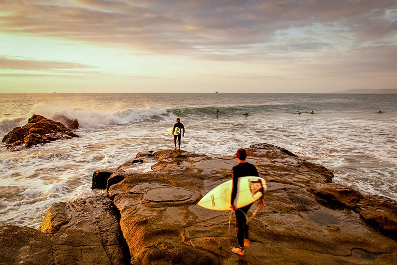 Two surfers walk out onto a rust-colored rock towards the surf at sunset. There are several other surfers already in the sea.