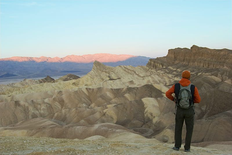 Sunrise in Death Valley National Park. A person stands with their back to the camera, they are wearing a woolly orange hat, an orange jumper, a grey backpack and grey trousers. They look over the undulating sandstone structures of Death Valley, the pink morning light has just started to touch the furthest peak.