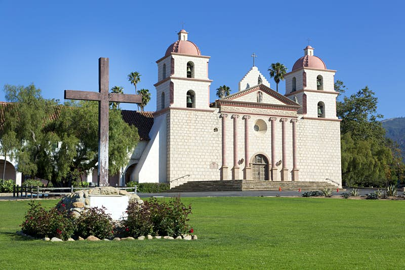 The Santa Barbara Mission. A large wooden cross is in the foreground, in the background there's a small white-brick church with red-domed turrets