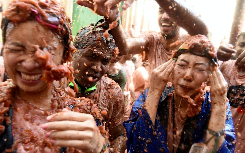 Revellers are covered with smashed tomato puree during the 'Tomatina' festival in Bunol. Everyone in the photo is being splattered with tomato pulp and squinting to try protect their eyes. It's pandemonium.