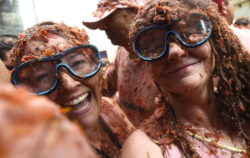 """Two revellers sporting diving masks pose covered up with smashed tomatoes, during the 'Tomatina' festival in Bunol, on August 29, 2018. - This iconic annual fiesta that takes place on the last Wednesday of August and has been billed as """"the world's biggest food fight"""". Two festival goers wear snorkelling goggles to protect their eyes from the tomato pulp"""