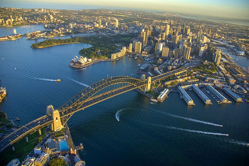 An aerial shot of Sydney Harbour at sunset. Boats leave wake trails in the water under the bridge.