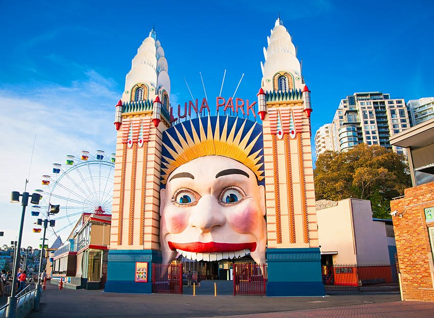 The Luna Park entrance has a large face smiling on the front, and people walk into its mouth to enter. Sydney, Australia