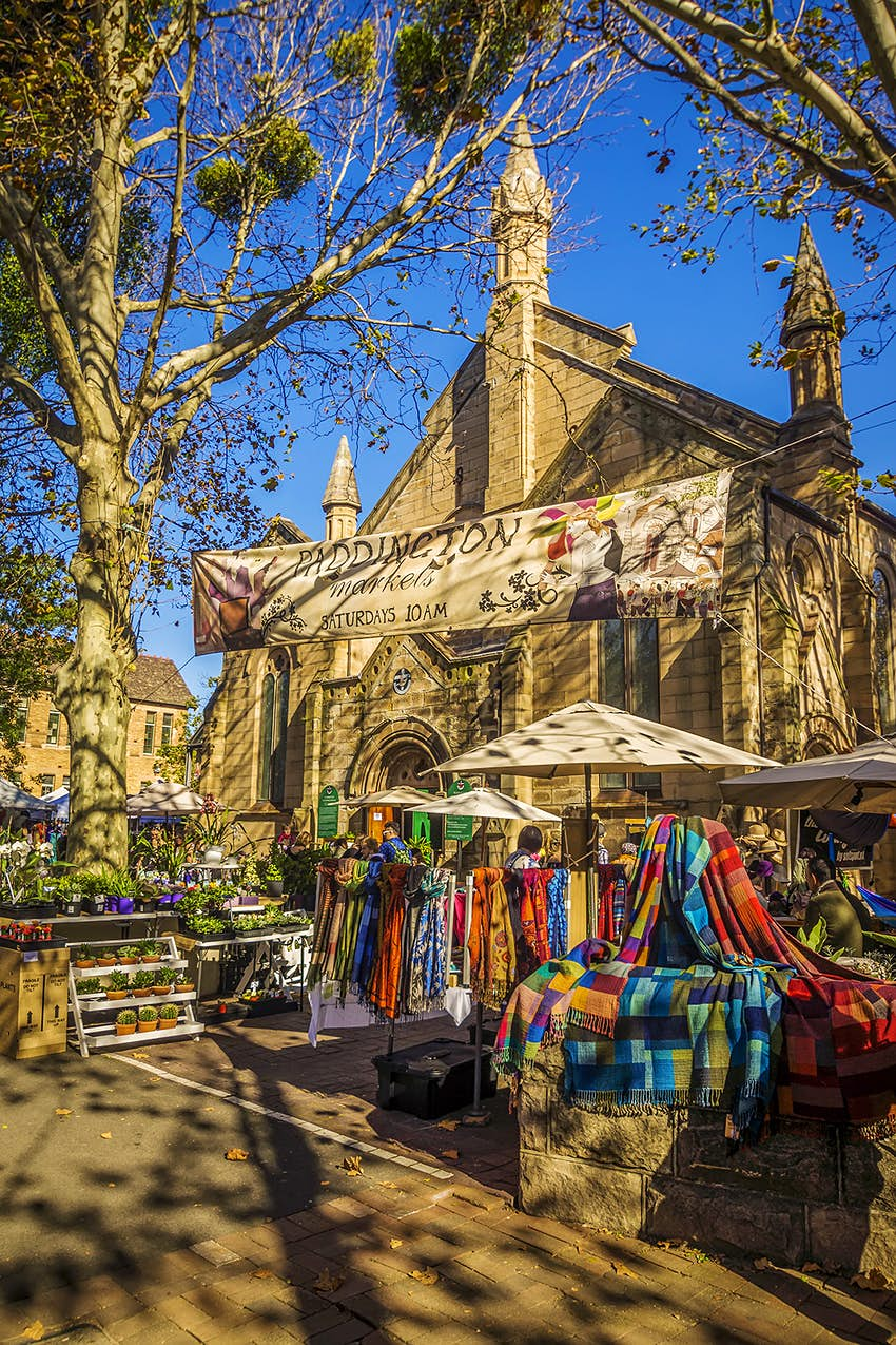 """Market stalls of clothing and plants are set up in front of an older church. The sunlight is golden and a sign that says """"Paddington"""" is strung between trees"""