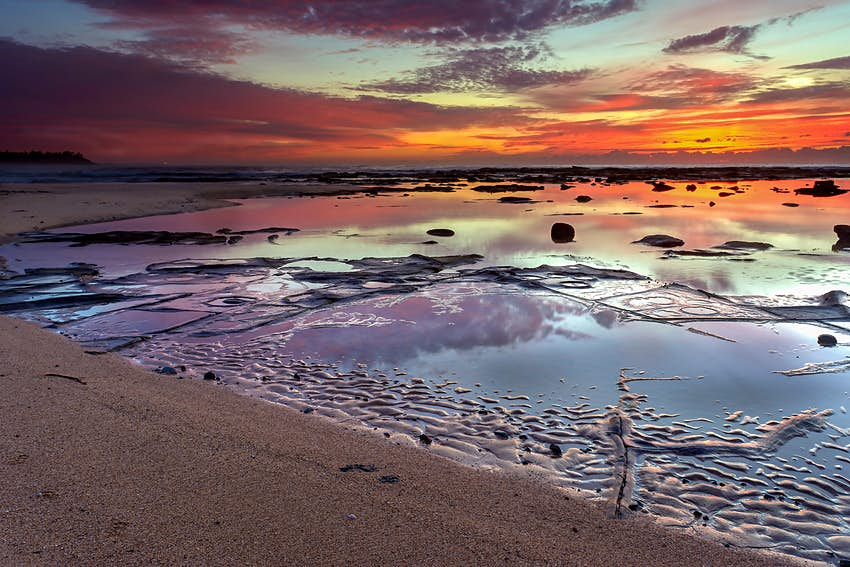A sunset reflects orange, red and purple off of tide pools at Shelley Beach. Sydney, Australia.