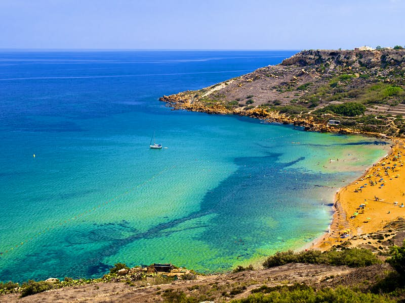 An aerial shot of Ramla Bay, with its terracotta-coloured sand and pale, light-blue waters