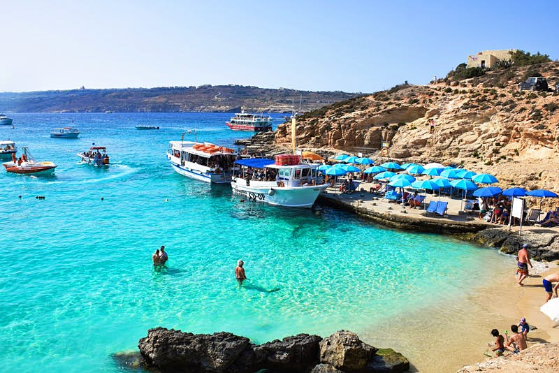 Malta's Blue Lagoon, a beach with shallow turquoise water, in which a few people swim while others sit on the sand. Further out a few boats are moored.
