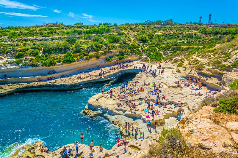 Groups of people relax on the rocks surrounding St Peter's Pool, a naturally formed sea pool
