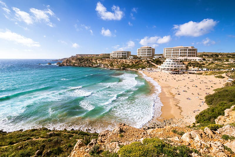 A sweeping view of Golden Bay in Malta with large waves lapping the beach, which is packed with sunbathers. In the distance a few hotels are perched on the top of the hill