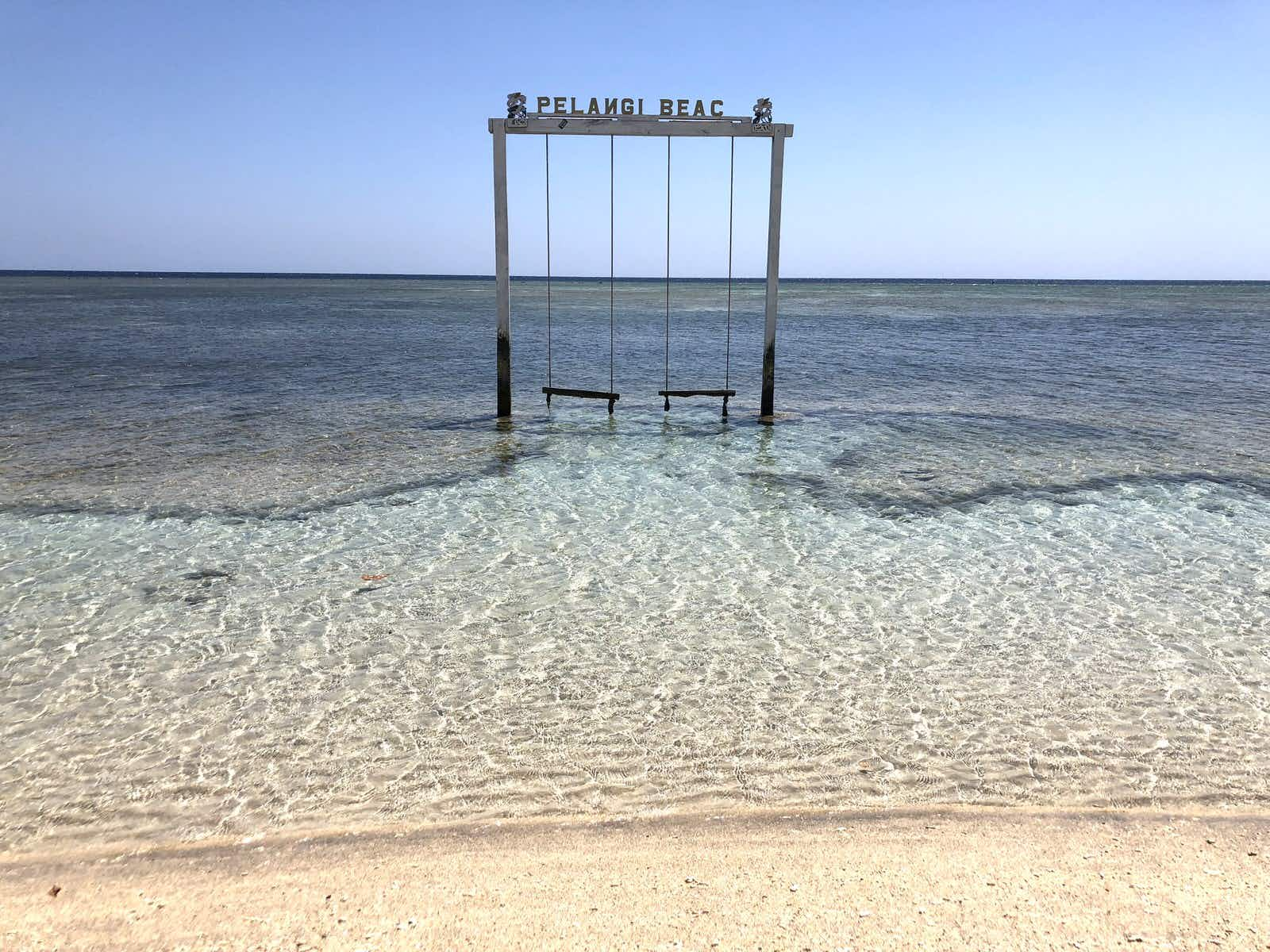 Gili Islands - a large two-seater wooden swing in crystal-clear water with the words 'Pelangi Beach' on the top of the frame © Mark Johanson / Lonely Planet
