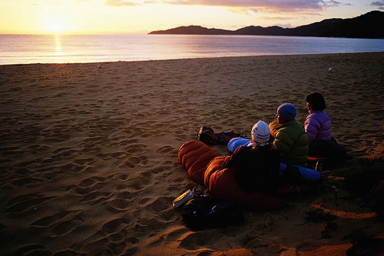 Three people sit on a sandy beach in sleeping bags watching the sunset