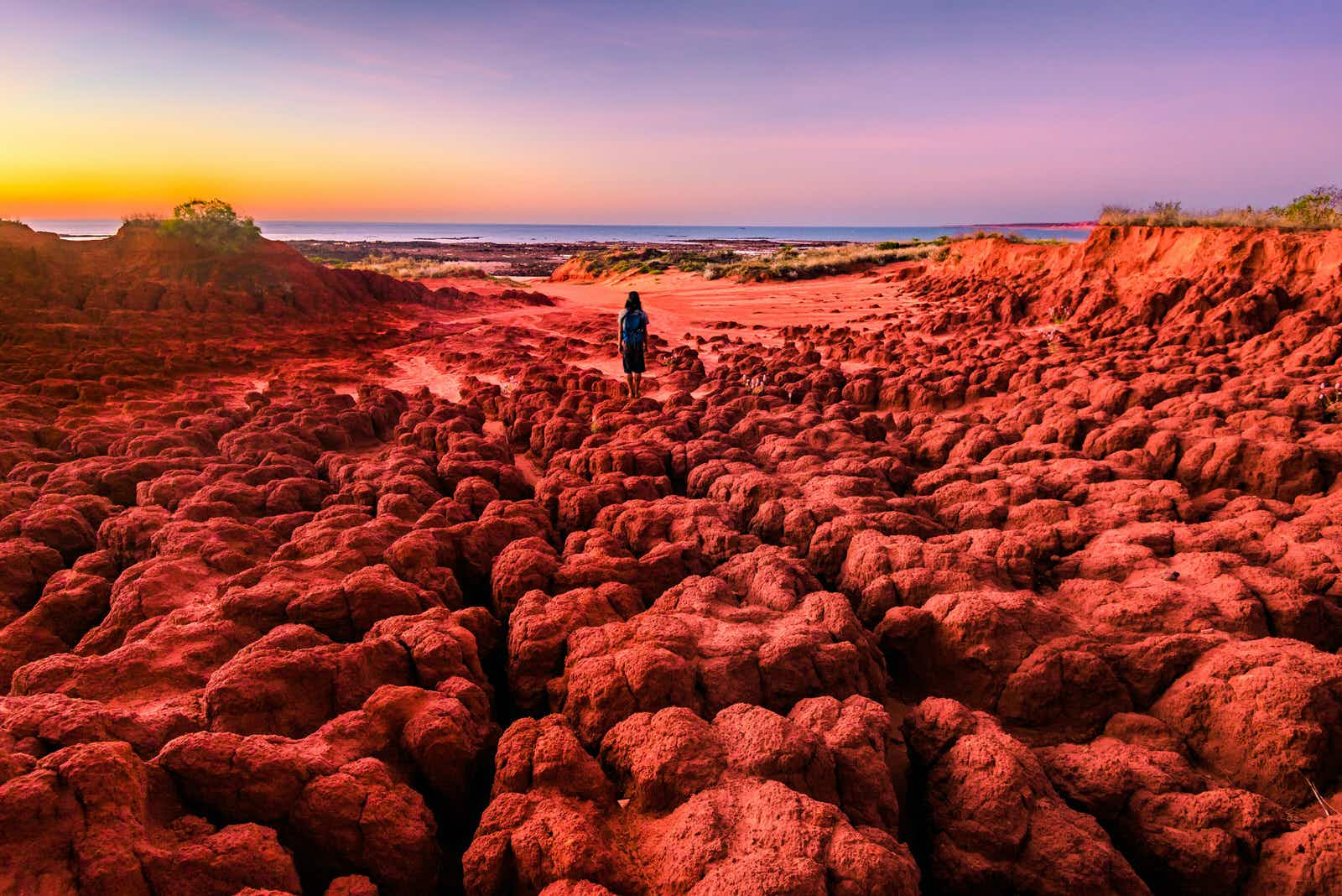 A woman looks out at the sunset from the red pindan soils of James Price Point at Dampier Peninsula. Western Australia