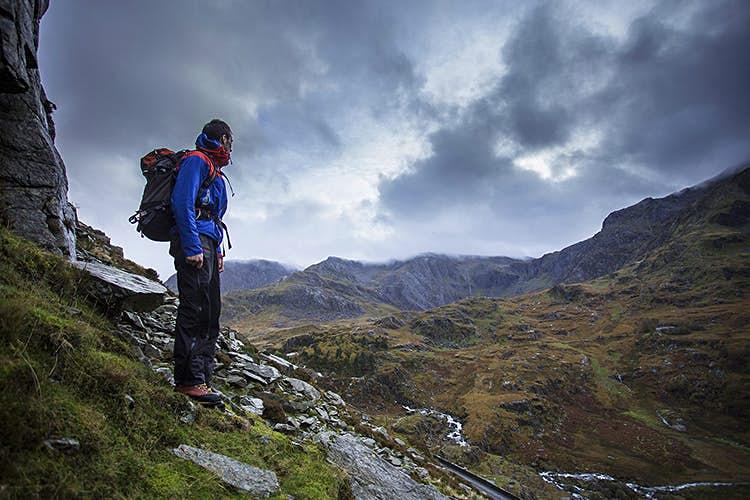 A man in hiking gear carrying a backpack stands on a rocky hillside surveying grey clouds that are rolling down the valley