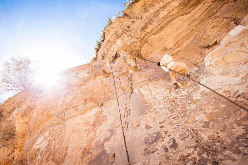 A monk climbs up to Debre Damo. Image by Philip Lee Harvey / Lonely Planet