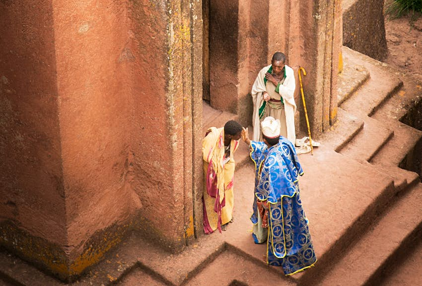 A priest blesses pilgrims outside the entrance to Bet Giyorgis. Image by Philip Lee Harvey / Lonely Planet