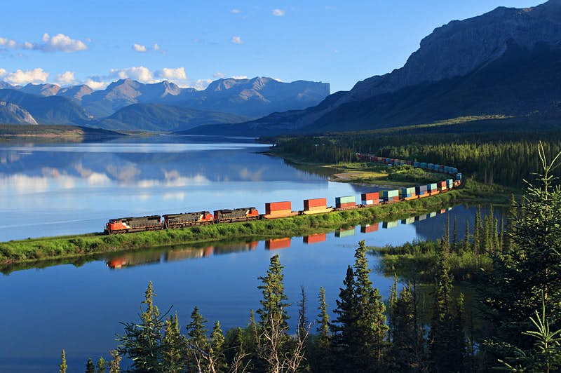 A freight train cruises through Swan Landing near Brule, Alberta; the train is reflected in the still waters of the lake while mountains are visible in the background