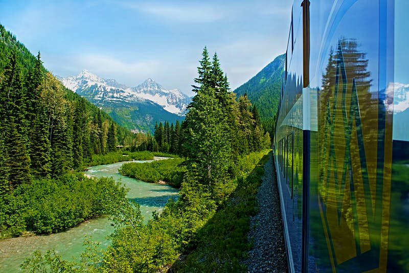 Image of a train passing through Canada's Banff National Park taken by a passenger out of a window; forests, rivers and mountains are visible