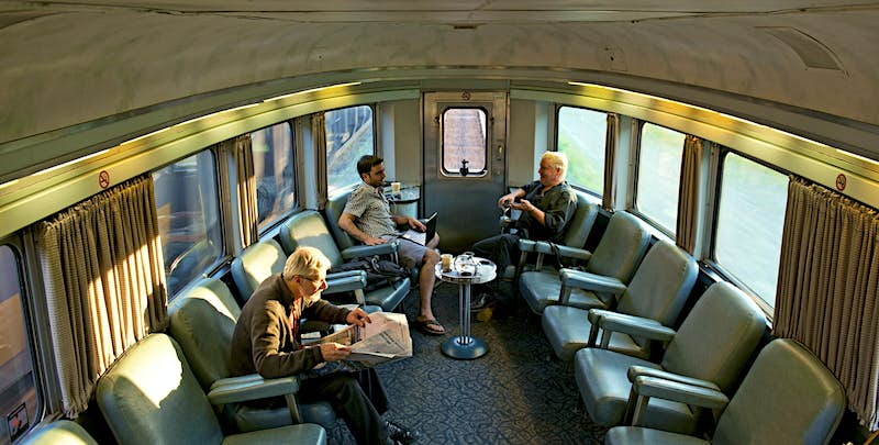 The interior of the Canadian train, with several passengers sitting on comfortable, reclining chairs that line the walls