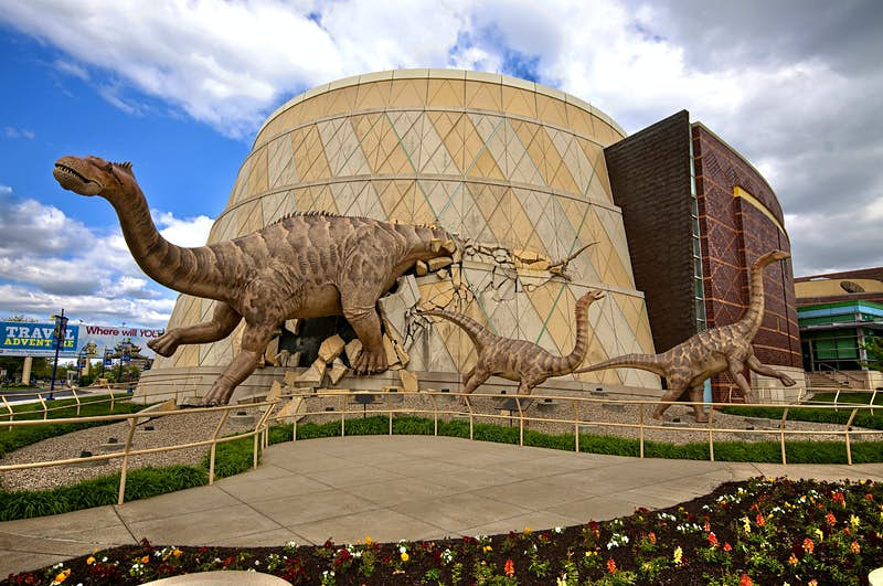 A dinosaur busts through the wall of the Children's Museum of Indianapolis. Imageby Lavengood Photography.