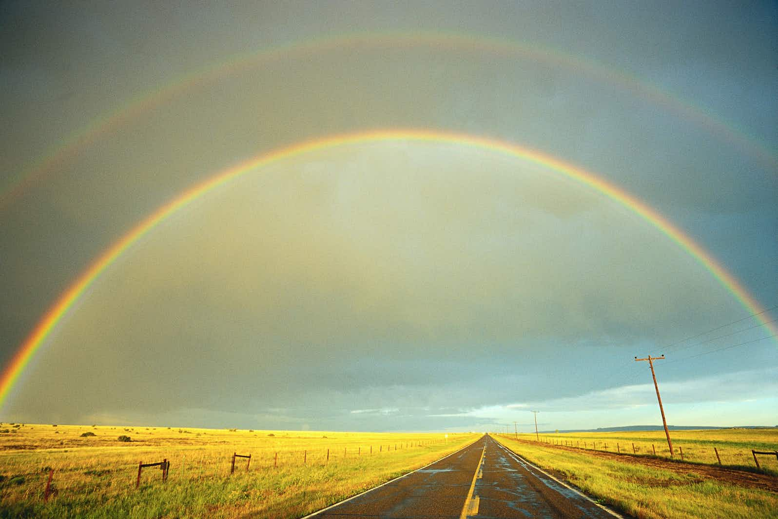 A rainbow stretches over a country road. Image by Fuse / Getty
