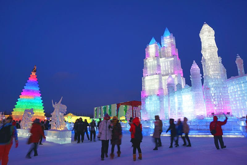 Colourful ice towers oversee Harbin's Ice and Snow World. Image by Anita Isalska / Lonely Planet